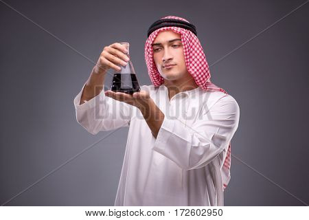 Arab with oil on gray background