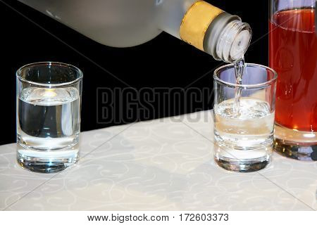 Filling the glasses with alcohol. Transparent vodka served to the dining table. The culture of drinking at the party ethanol for alcoholics.