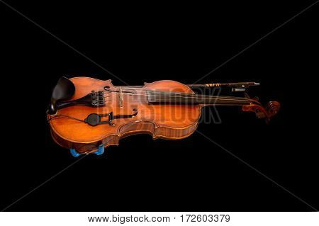 Violin and bow isolated on black background. A musical stringed instrument for musical performance. Classical orchestral music.