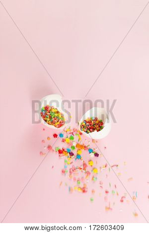 White Easter eggs on a light pink background broken egg with colored decorations minimalistic design vertical shot
