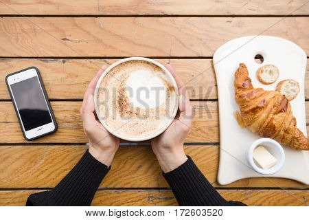 Top view on woman's hands holding big cup with cappuccino coffee and fresh French croissant on a wooden table in outdoor cafe. Breakfast with coffee and bread.