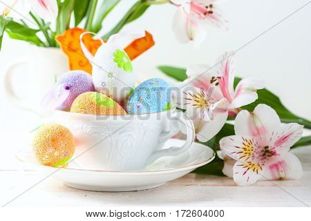 Easter Eggs With Spring Flowers On Table.