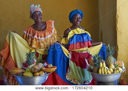 CARTAGENA DE INDIAS, COLOMBIA - JANUARY 24, 2017: Women in traditional costume posing for a photograph whilst selling fresh fruit in the historic walled city of Cartagena de Indias in Colombia