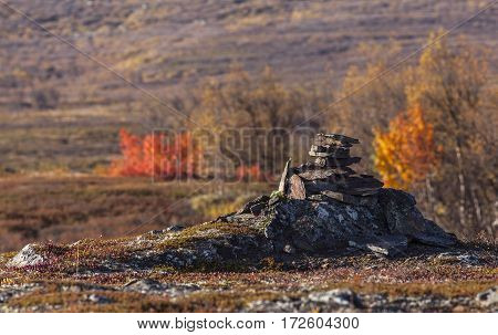 Stack of stones along a mountain trail. Track and colorful bushes in the background.