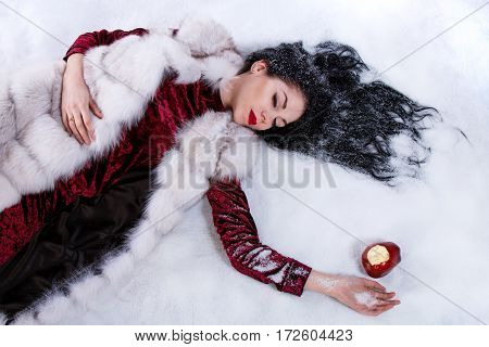 Woman Laying On A Snow Near The Bitten Apple