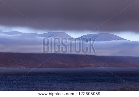 Dark and cloudy evening in the Nordic mountain, rainy clouds. Lake this side and mountain in the background.