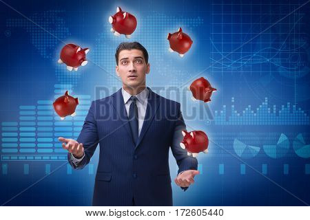 Businessman juggling with piggybanks in business concept
