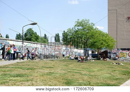 BERLIN, GERMANY - MAY 09: Tourists visiting and young people sunbathing on the lawn at the back of the East Side Gallery on May 09 2016 in Berlin.