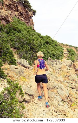 Trail running woman cross country running in mountains on summer beautiful day. Training and working out runner jogging and exercising outdoors in nature rocky footpath on Crete Greece