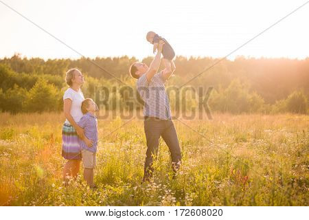 Happy family with two boys on a summer meadow enjoying sunset. Mother and father with kid boy and cute baby. Family together parents with their little children. Father raising baby up in the air.