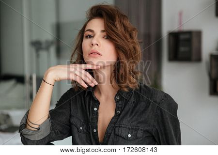 Photo of young attractive lady sitting on chair at home indoors. Looking at camera.