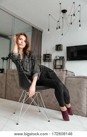 Photo of young amazing woman sitting on stool at home indoors. Looking at camera.