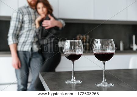 Photo of young loving couple standing in kitchen at home indoors. Focus on alcohol in glass.