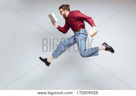 Male nerd jumping in studio with books in hands