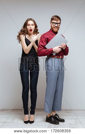 Vertical image of Surprised woman with Male nerd in eyeglasses which holding laptop. Isolated gray background