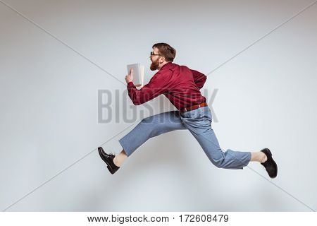 Male nerd running with books in studio. Isolated gray background