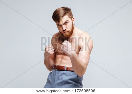 Serious Male nerd as fighter with naked torso. Isolated gray background