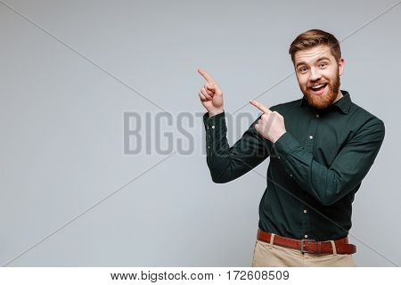Happy Bearded man in green shirt with open which pointing up. Isolated gray background