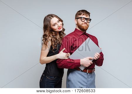 Smiling Woman from back of Male nerd in eyeglasses which holding laptop. Isolated gray background