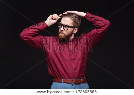 Male nerd combing his hair and looking away