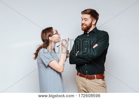 Female nerd in funny eyeglasses standing near the bearded man and writing something