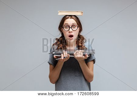 Surprised Female nerd in funny eyeglasses with book on head which holding laptop and notebook in hands