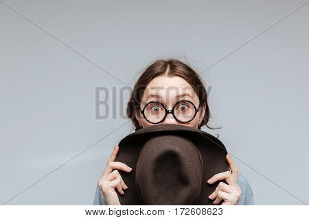 Surprised Female nerd in eyeglasses which looking behind the hat over gray background