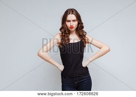 Displeased woman with arms on hip looking at camera. Isolated gray background