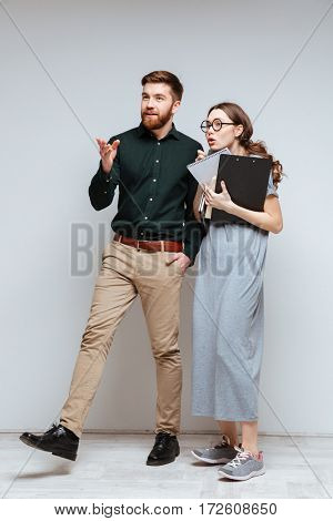 Vertical image of cool bearded man with Female nerd. Isolated gray background