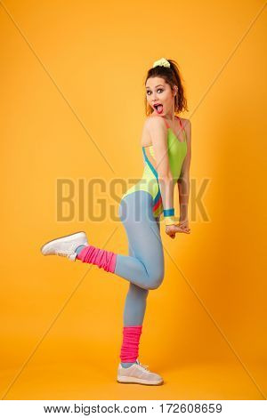 Full length of amazed cute sportswoman standing and shouting over yellow background