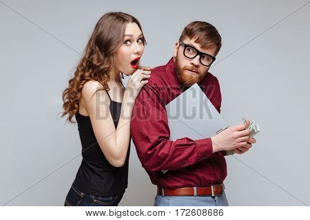 Shocked Young Woman from back of Cunning Male nerd in eyeglasses which recounts the money and holding laptop