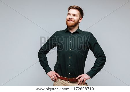 Smiling Bearded man in green shirt which posing with arms at hip and looking at camera