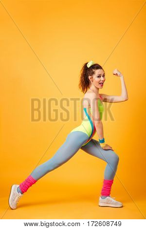 Full length of happy pretty young fitness woman exercising and showing biceps over yellow background