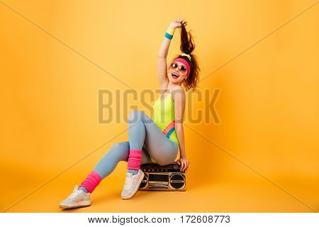 Cheerful lovely young woman athlete sitting on retro boombox and having fun over yellow background