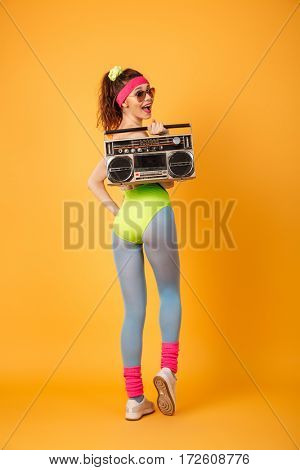 Smiling pretty young fitness woman holding retro boombox and looking back over yellow background