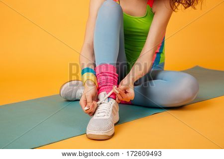 Closeup of sportswoman sitting on mat and tying shoelaces over yellow background