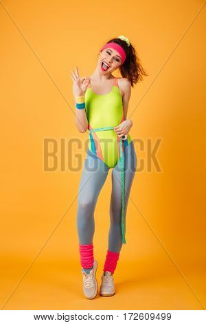 Happy young woman athlete measuring waist with tape and showing ok sign over yellow background