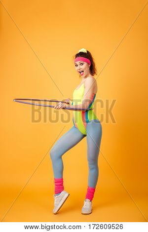 Cheerful young fitness woman working out and using hula hoop over yellow background
