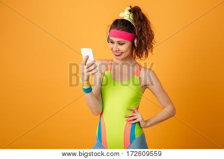 Smiling young woman athlete standing and listening to music from cell phone over yellow background