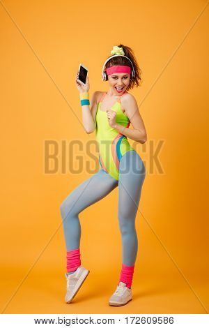 Cheerful young sportswoman in headphones listening to music from blank screen mobile phone over yellow background