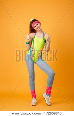 Cheerful young sportswoman with jumping rope standing and showing thumbs up over yellow background