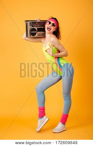 Cheerful pretty young sportswoman in sunglasses holding boombox and showing ok sign over yellow background