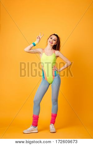 Cheerful attractive young woman athlete standing and showing peace sign over yellow background