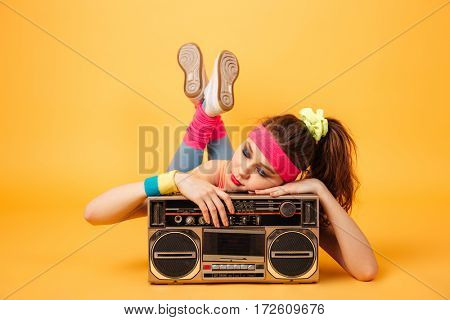 Cute lovely young woman athlete lying and sleeping on retro boombox over yellow background