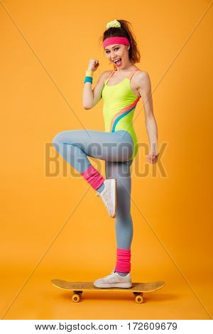 Full length of smiling young woman athlete standing on skateboard over yellow background