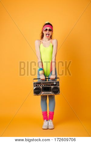 Happy excited young woman athlete holding retro boombox and shouting over yellow background