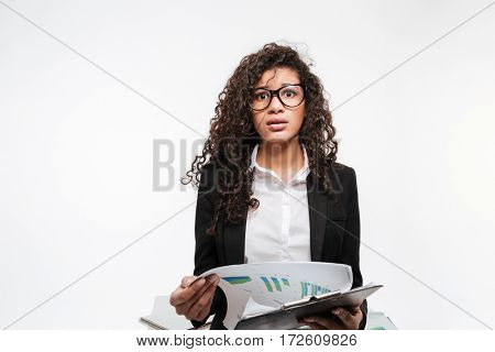 Photo of shocked african business lady wearing glasses reading gazette over white background. Looking at camera.