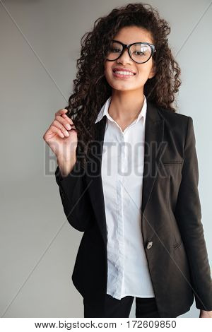 Photo of happy african business lady wearing glasses standing over grey background. Looking at camera.
