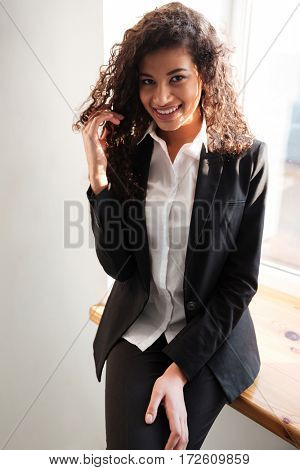 Photo of amazing african businesswoman standing over white background near window. Looking at camera.