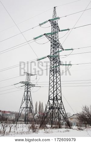 high voltage post with a cloudy sky in the place in winter